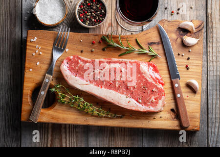 Fresh raw Prime Black Angus beef steaks with spices and red wine on wooden board: Striploin, Rib Eye. Top view. On a dark rustic table - Stock Photo