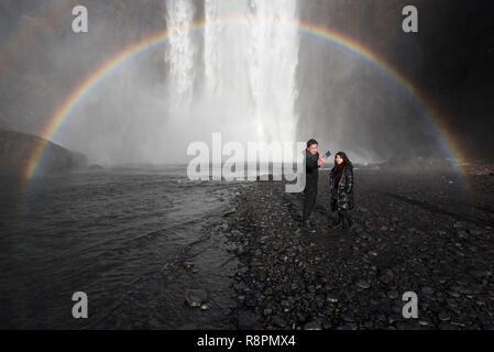 Iceland, South Iceland, Sudurland Region, Skogar, couple in front of Skogafoss, rainbow, selfie - Stock Photo