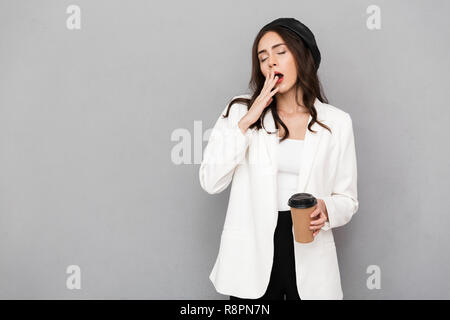 Full length portrait of a young sleepy businesswoman over gray background, holding takeaway coffee, yawning - Stock Photo