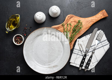 Empty plate, cutlery, olive wooden cutting board and spices on black background. Top view. Restaurant table setting, food background or menu - Stock Photo