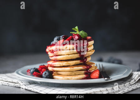 Pancakes with berry sauce and berries over dark background. Pancakes stack with blueberries, strawberries and sweet sauce. Closeup view - Stock Photo