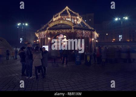 13 DEC 2018, Romania, Bucharest. House of Santa Claus at Christmas Market at Romanian Parliament. Long exposure image - Stock Photo