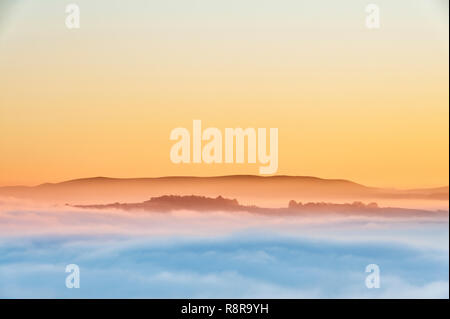 On Stonewall Hill in the Welsh borders near Knighton, UK. Evening view of Hay Bluff and the Black Mountains showing the valleys filled with thick fog - Stock Photo