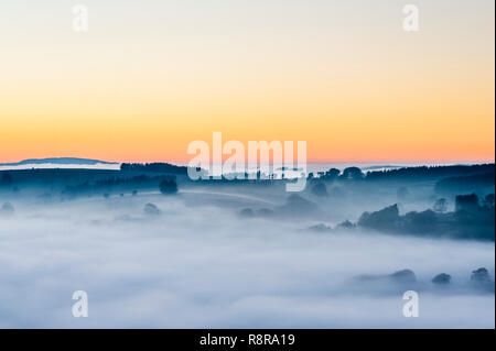 On the border between England and Wales near Knighton, Powys, UK. Evening view west from Stonewall Hill showing the valleys filled with thick fog - Stock Photo