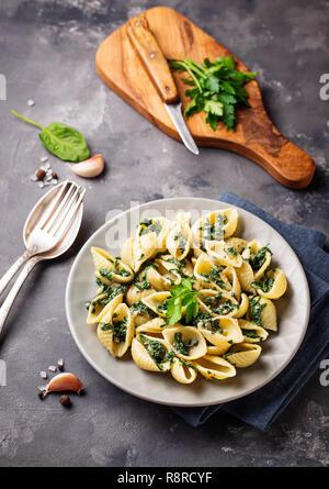 Conchiglioni pasta with spinach in creamy sauce  - Stock Photo