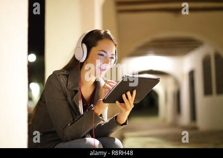 Relaxed woman wearing headphones watching media in a tablet in the night in the street