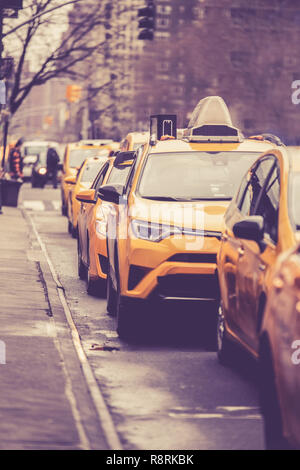 Vintage toned image of Line of New York City yellow taxicabs on street in Manhattan - Stock Photo