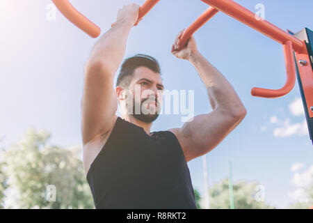 Closeup of strong athlete doing pull-up on horizontal bar.Mans fitness with blue sky in the background and open space around him. Young man with sportive clothes in the city. - Stock Photo