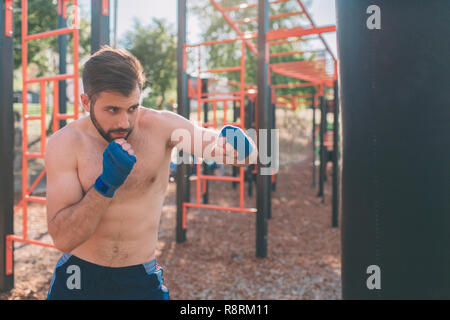 Young man boxing workout. Boxer Exercise Athletic Boxing Concept. boxer punch hand by punching bag. - Stock Photo