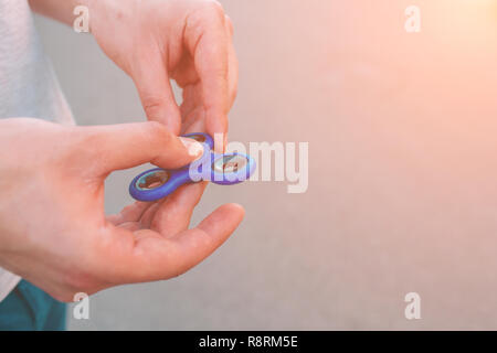 Young man holding and playing with fidget spinner. - Stock Photo