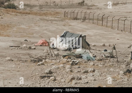 Bedouin houses in the desert near Dead Sea. Poor regions of the world. A indigent Bedouin sitting at the tent. Poverty in Jordan. middle East - Stock Photo