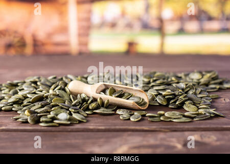 Lot of whole hulled pumpkin seeds with wooden scoop with cart in background - Stock Photo