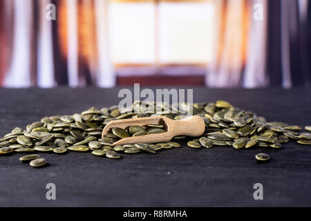 Lot of whole hulled pumpkin seeds with wooden scoop with silk curtains behind - Stock Photo