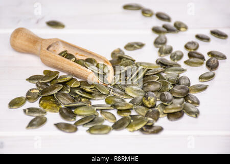 Lot of whole hulled pumpkin seeds with wooden scoop on white wood - Stock Photo