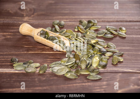 Lot of whole hulled pumpkin seeds with wooden scoop on brown wood - Stock Photo