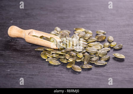 Lot of whole hulled pumpkin seeds with wooden scoop on grey stone - Stock Photo