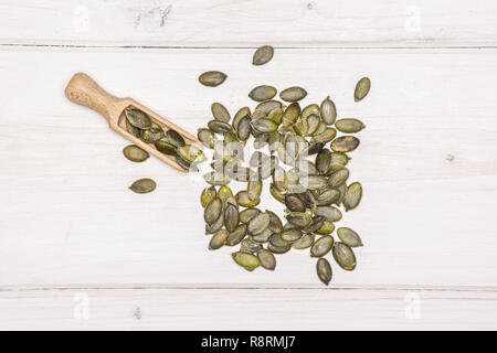 Lot of whole hulled pumpkin seeds with wooden scoop flatlay on white wood - Stock Photo