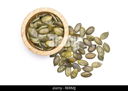 Lot of whole raw hulled pumpkin seeds with wooden bowl flatlay isolated on white background - Stock Photo