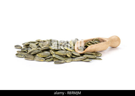 Lot of whole hulled pumpkin seeds with wooden scoop isolated on white background - Stock Photo