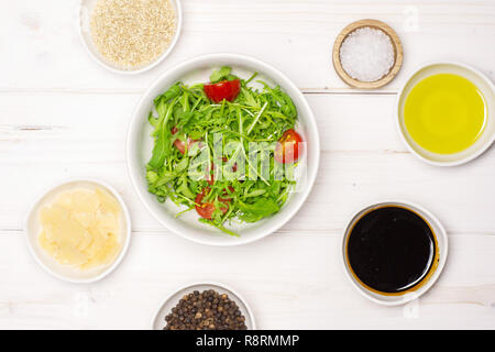 Mixed arugula leaves and sliced cherry tomatoes. recipe step by step arugula salad in a grey ceramic bowl flatlay on white wood - Stock Photo
