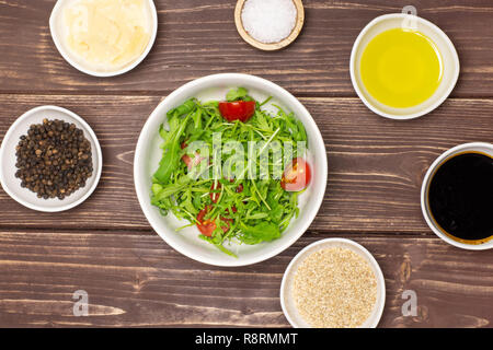 Mixed arugula leaves and sliced cherry tomatoes. recipe step by step arugula salad in a grey ceramic bowl flatlay on brown wood - Stock Photo