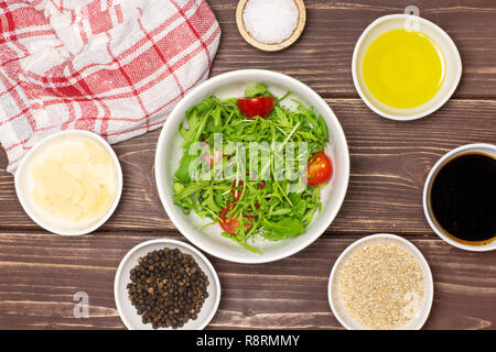 Mixed arugula leaves and sliced cherry tomatoes. recipe step by step arugula salad with a tea towel flatlay on brown wood - Stock Photo