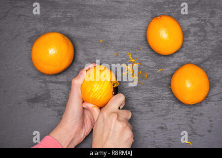 Woman hands are scraping orange zest. recipe step by step hot red mulled wine flatlay on grey stone - Stock Photo