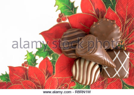 Chocolate sweet food for Christmas season. Five chocolates over a poinsettia paper napkin. The image of chocolate candies or bon bons are set on a Chr - Stock Photo