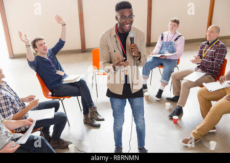Man with microphone talking, leading group therapy - Stock Photo