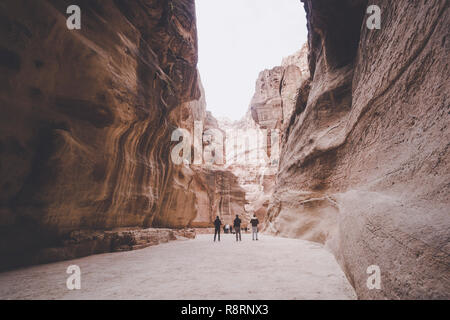 Siq, the narrow slot-canyon that serves as the entrance passage to the hidden city of Petra, Jordan, seen here with tourists walking. UNESCO World Her - Stock Photo