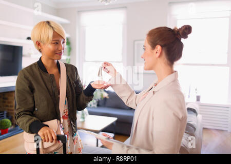 Real estate agent giving house rental keys to young woman - Stock Photo