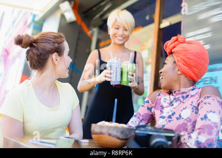 Waitress serving smoothies to women friends at sidewalk cafe - Stock Photo