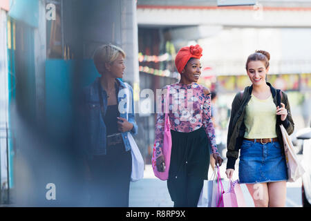 Young women friends walking with shopping bags on urban sidewalk - Stock Photo