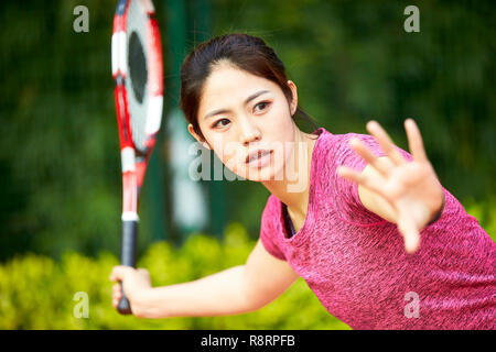 young asian woman female tennis player hitting ball with forehand - Stock Photo