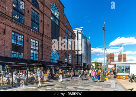 Oslo, Norway - June 5th 2018 - Big group of people walking in front of a large building in Oslo in a summer blue sky day in Norway - Stock Photo