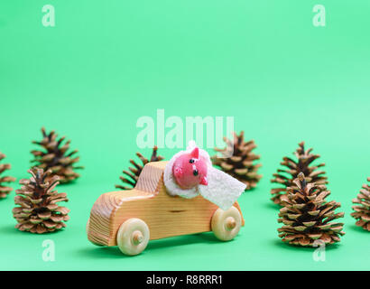wooden children's car in the midst of cones on a green background, new year holiday concept - Stock Photo