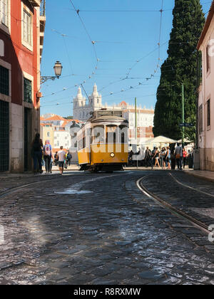 Lisbon, Portugal - October 01, 2018 : Vintage yellow tram on line 28 in Alfama against Church of Sao Vicente of Fora - Stock Photo