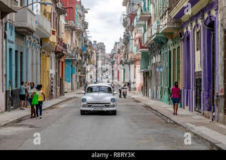 Street scene with white American car near the Malacon in Havana, Cuba.
