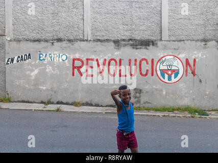 Sweet little Cuban boy giving the thumbs up in front of a sign saying Revolucion in Havana Cuba - Stock Photo
