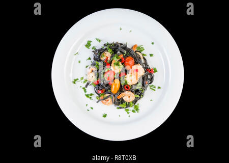 Black squid ink Fettuccine pasta with prawns or shrimps cherry tomatoes, parsley, chili in wine and butter sauce. - Stock Photo