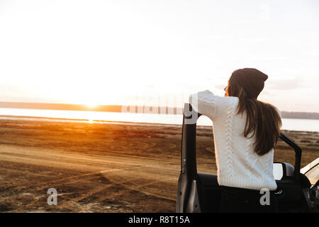 Beautiful young girl standing at her car, watching sunset - Stock Photo