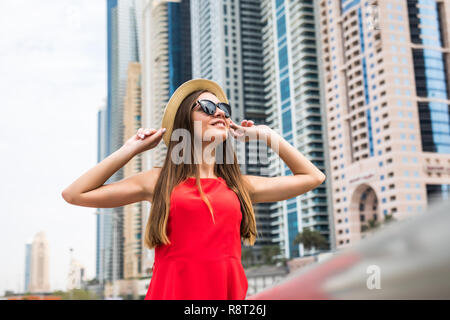 Portrait of young woman wearing in red dress and sunglasses, straw hat in front of skycrapers in modern city - Stock Photo