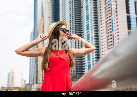 Portrait of young pretty woman wearing in red dress and sunglasses, straw hat in front of skycrapers in modern city - Stock Photo