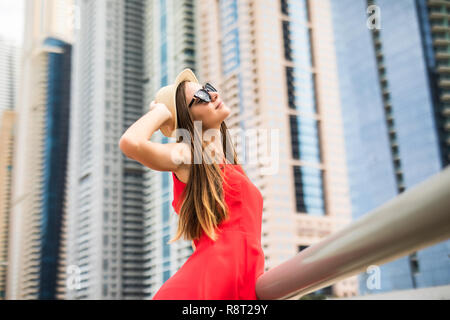 Young woman holding straw hat wearing in red dress and sunglasses in front of skycrapers. - Stock Photo