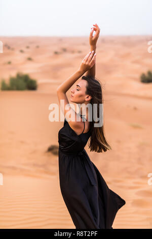 Young beautiful Caucasian woman posing in a traditional Emirati dress - abaya in Empty Quarter desert landscape. Abu Dhabi, UAE. - Stock Photo