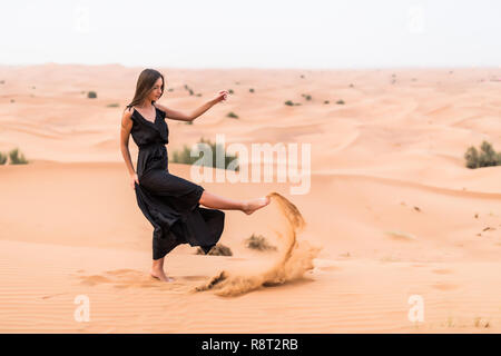Woman with a traditional Emirati dress in desert. - Stock Photo