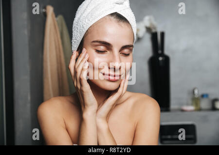 Photo of adorable woman with towel on head touching her face after bath while standing in bathroom - Stock Photo