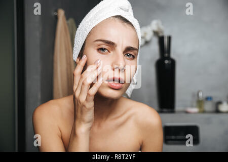 Photo of displeased woman with towel on head touching her face after bath while standing in bathroom - Stock Photo