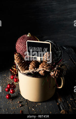 some different cozy christmas ornaments in a rustic brown enamel pot and a black signboard with the text eguberri on, merry christmas written in basqu - Stock Photo