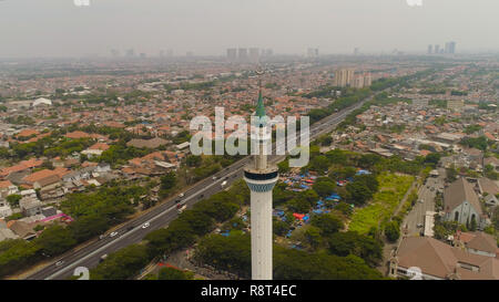 aerial view minaret mosque Al Akbar against city Surabaya highway, skyscrapers, buildings and houses. mosque in Indonesia Al Akbar in Surabaya, Indonesia. beautiful mosque with minarets on island Java Indonesia. - Stock Photo